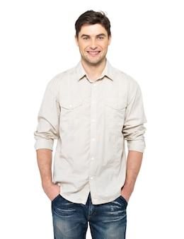 Ritratto dell'uomo bello felice sorridente in casuals - isolato sulla parete bianca