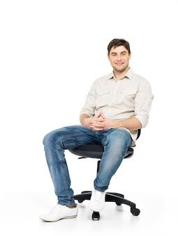 Il ritratto dell'uomo felice sorridente si siede sulla sedia dell'ufficio isolata su bianco.