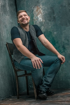 Portrait of smiling happy man sitting on the wooden chair on gray studio