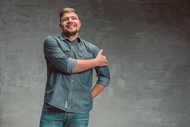 Portrait of smiling happy man standing in studio