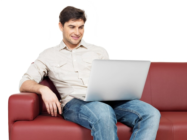 Portrait of smiling happy man with laptop sits on divan, isolated on white.