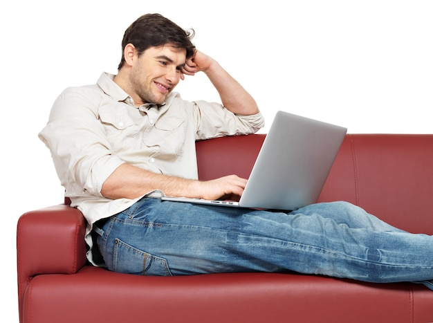 Il ritratto dell'uomo felice sorridente con il computer portatile si siede sul divano, isolato su bianco.