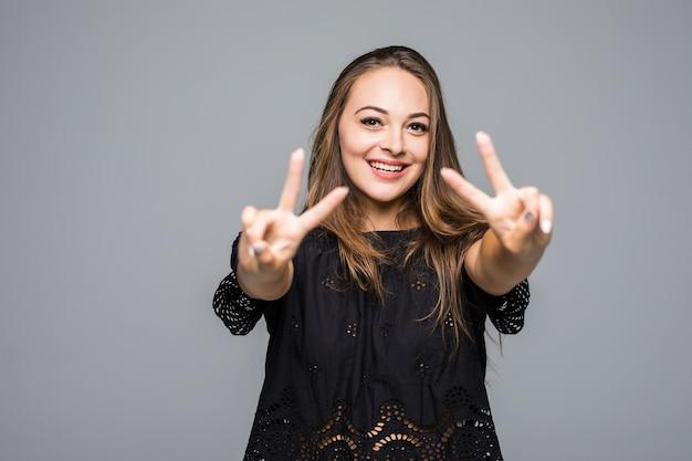 Ritratto di una donna felice sorridente che mostra il segno di vittoria su gray