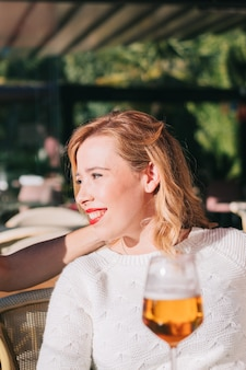 Portrait of a smiling and happy young adult caucasian woman drinking in a restaurant with a group of friends.