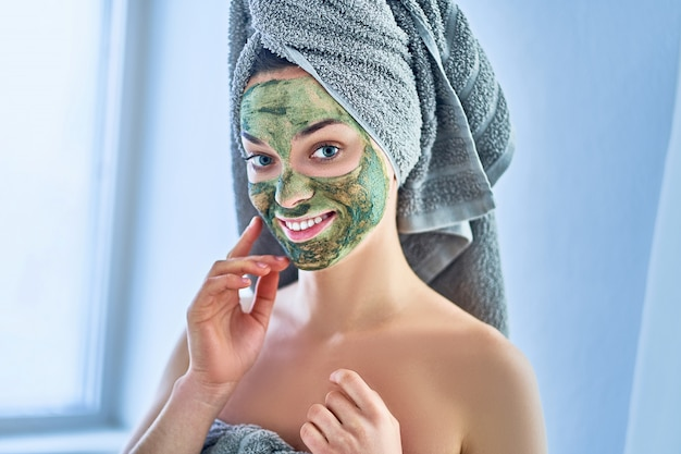 Portrait of smiling happy young healthy woman in bath towel with green facial clay mask during spa day at home. face skin care