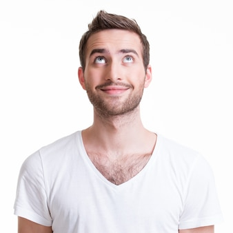 Ritratto del giovane felice sorridente che osserva in su - isolato su bianco