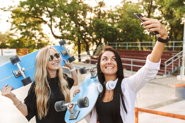 Portrait of a smiling happy young pleased teenager girls skaters friends in park outdoors with skateboards using mobile phone take a selfie.