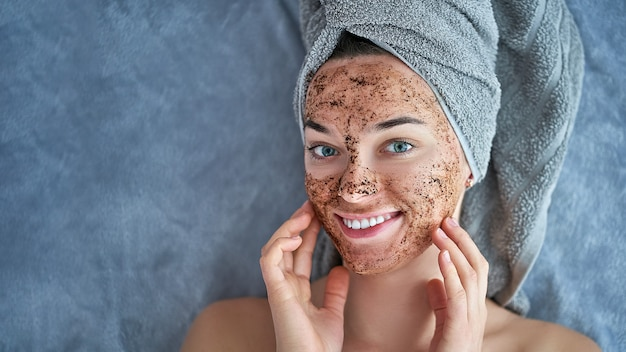 Portrait of smiling healthy female in bath towel with natural cleansing face coffee scrub after shower