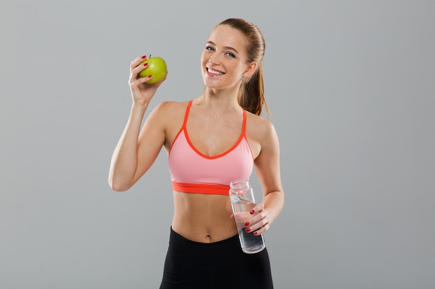 Portrait of smiling healthy sports girl holding green apple