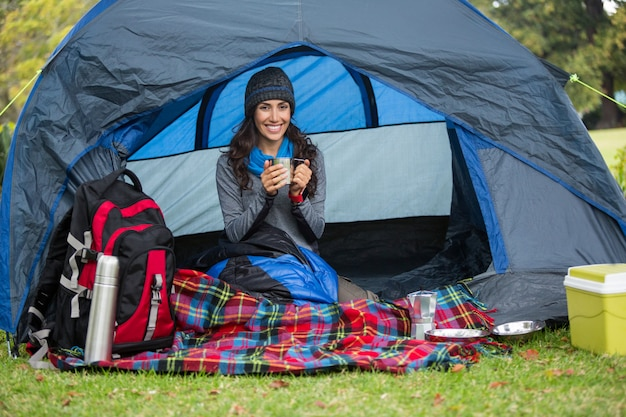 Portrait of smiling hiker having a cup of coffee in tent