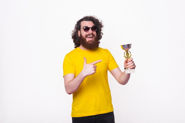 Portrait of smiling hipster man with curly hair pointing at champion cup