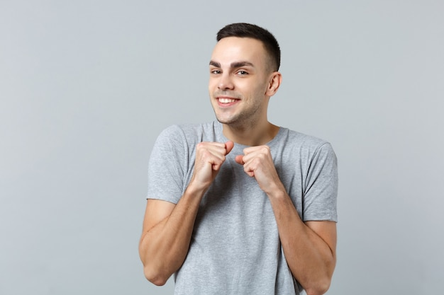 Portrait of smiling joyful young man in casual clothes and clenching fists