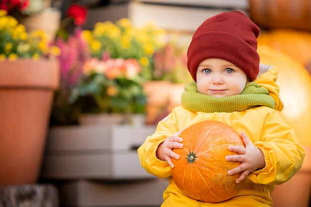 Portrait of a smiling kid in a bright yellow overalls with an orange pumpkin in his hands at the autumn fair.