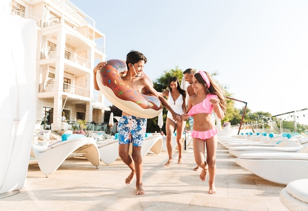Portrait of smiling kids and parents walking near swimming pool, and carrying rubber ring outside hotel during vacation