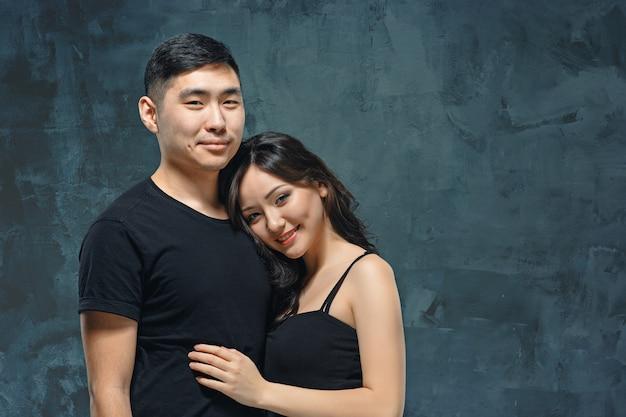 Portrait of smiling korean couple on a gray studio