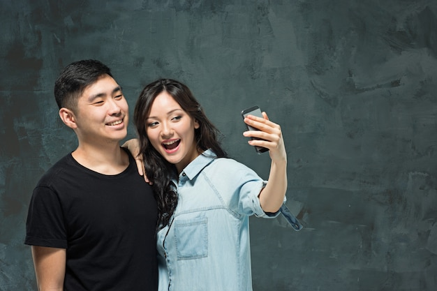 Portrait of smiling korean couple on a gray wall