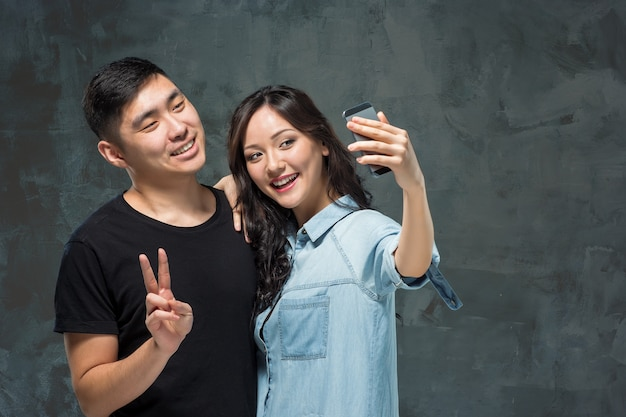 Portrait of smiling korean couple making selfie photo on a gray studio