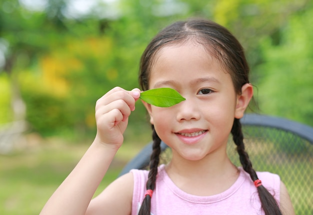 Portrait of smiling little asian child girl holding a green leaf closing right eye in green garden background.