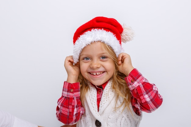 Portrait of smiling little blonde girl in santa hat on white  backgrounds