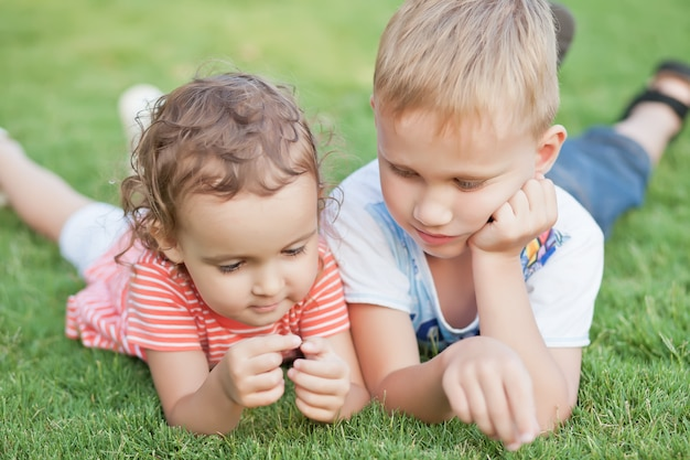Portrait of a smiling little girl and boy lying on green grass.