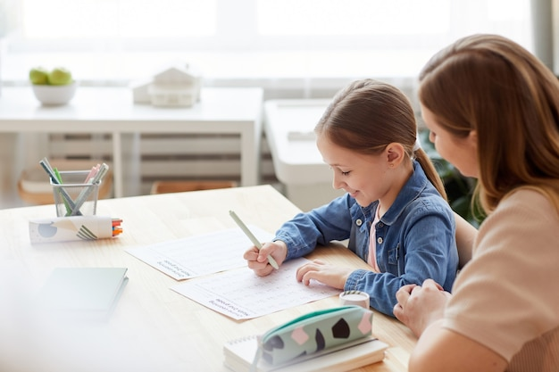 Portrait of smiling little girl doing math test for online school while studying at home with caring mother or tutor helping her, copy space
