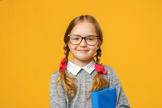 Portrait of a smiling little girl in glasses with a book.