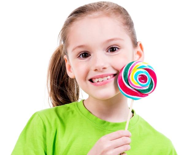 Ritratto di bambina sorridente in maglietta verde con caramelle colorate - isolato su bianco.