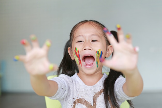 Portrait of smiling little girl looking through her colorful hands and cheek painted in kids room.
