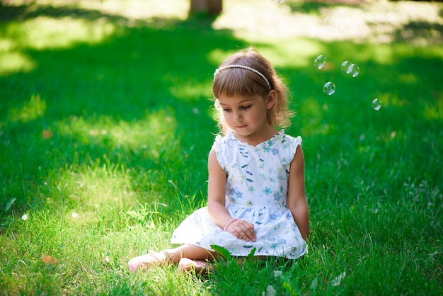 Portrait of a smiling little girl sitting on green grass.