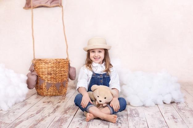 세로 풍선, 별과 구름의 벽에 앉아서 테 디 베어를 들고 어린 소녀 미소. 소녀는 장난감 어린이 방에서 재생합니다. 어린 시절. 아이는 휴가 선물을 보유하고 있습니다. 생신