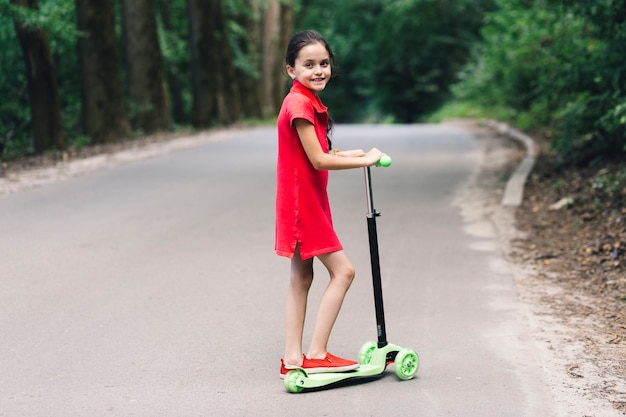 Portrait of a smiling little girl standing over push scooter on road