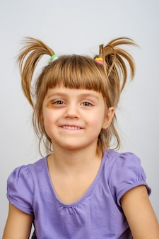 Portrait of smiling little girl with pigtails and bruise under the eye.