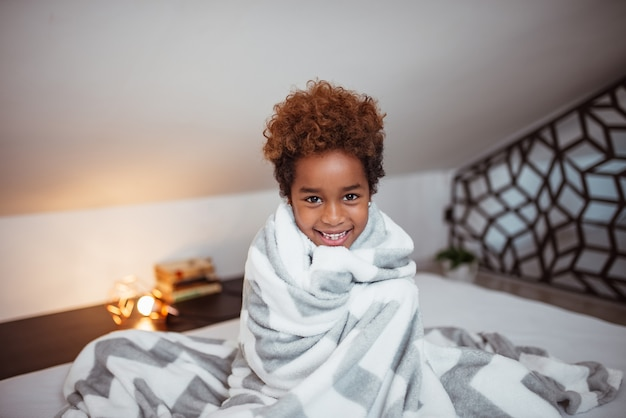 Portrait of a smiling little mixed-race girl with blanket sitting on bed and looking at camera.