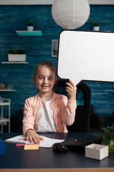 Portrait of smiling little schoolchild holding white board looking into camera