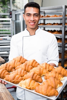 Portrait of a smiling male baker holding tray of baked croissant