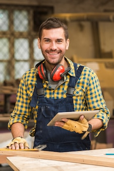 Portrait of a smiling male carpenter holding digital tablet in hand looking at camera
