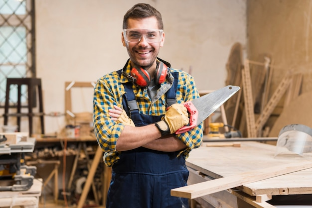 Portrait of a smiling male carpenter holding handsaw looking at camera