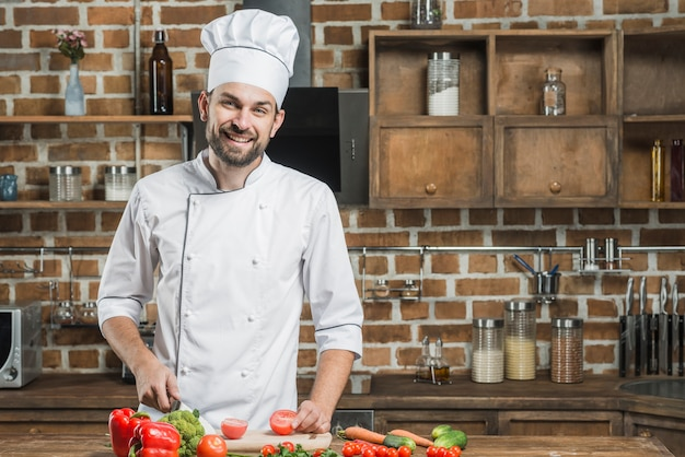 Portrait of smiling male chef standing behind the kitchen counter cutting vegetables