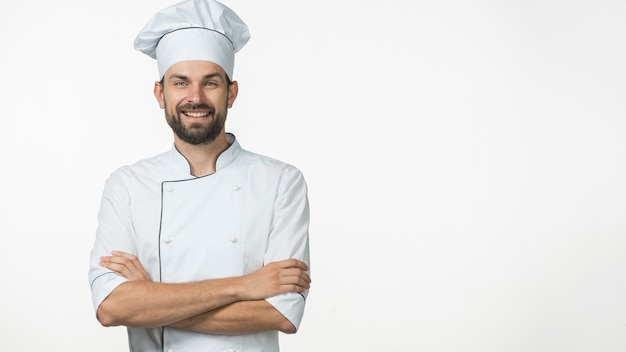Portrait of smiling male chef in white uniform isolated over white background