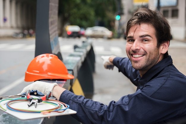 Portrait of smiling male electrician pointing with hard hat and equipment on street
