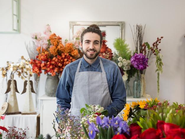 Ritratto di un fiorista maschio sorridente con i fiori variopinti nel negozio