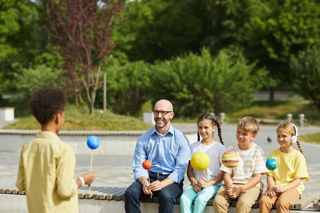Portrait of smiling male teacher listening to boy giving presentation on astronomy while sitting with group of children and enjoying outdoor lesson in sunlight, copy space