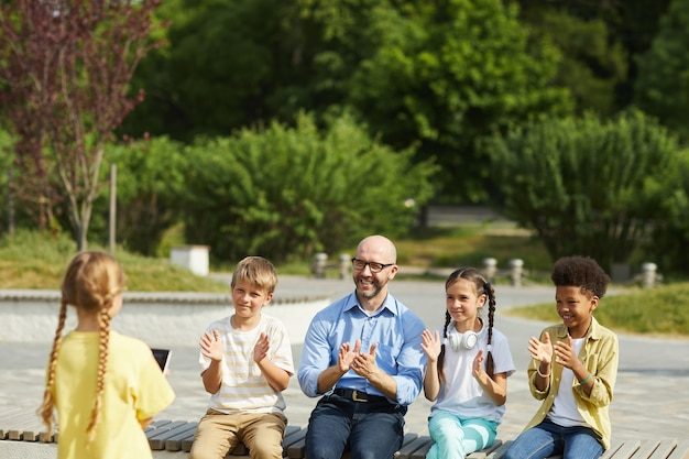 Portrait of smiling male teacher with group of children applauding to little girl giving presentation while enjoying outdoor lesson in sunlight, copy space