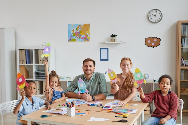 Portrait of smiling male teacher with multi-ethnic group of kids showing pictures of space rockets while enjoying art and craft lesson in preschool or development center