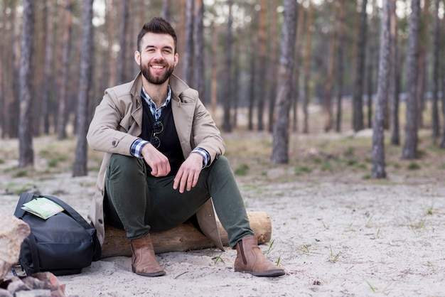 Portrait of a smiling male traveler sitting on beach with his backpack