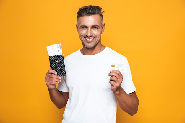 Portrait of smiling man 30s in white t-shirt holding credit card and travel tickets isolated on yellow