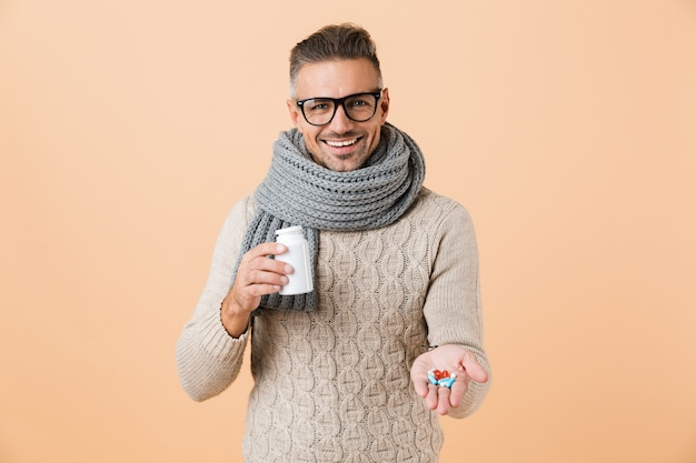 Portrait of a smiling man dressed in sweater and scarf standing isolated over beige wall, showing pills capsules