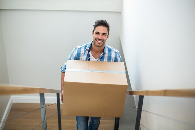 Portrait of smiling man holding cardboard box while climbing steps