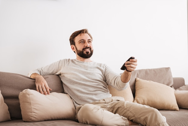 Portrait of a smiling man holding remote control
