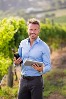 Portrait of smiling man holding wine bottle and tablet